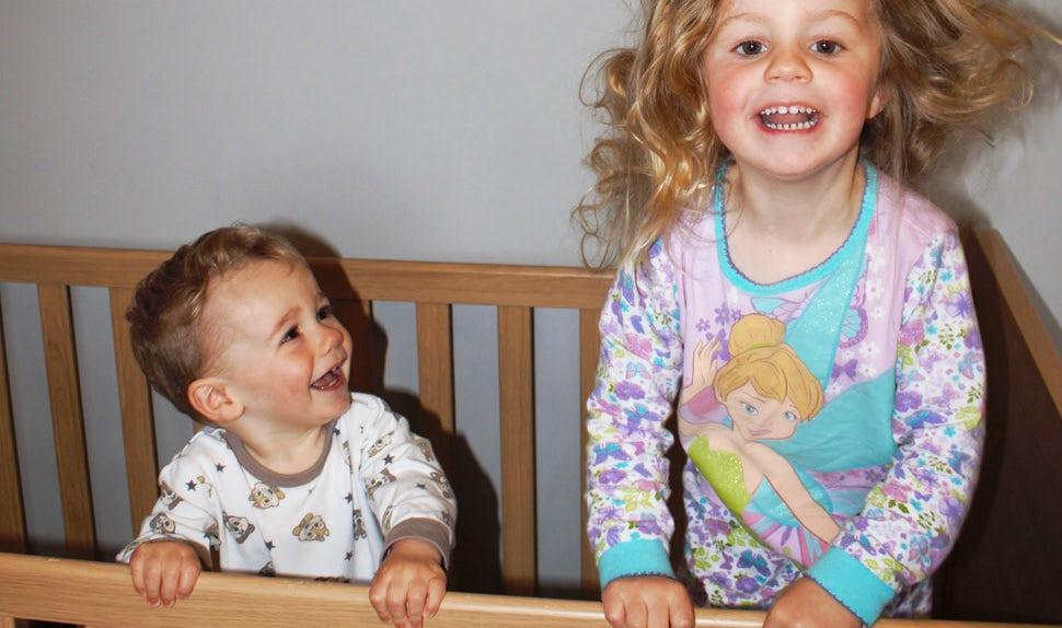 BABYBJÖRN Föräldramagasin – Barn som inte vill sova, två glada och klarvakna syskon i en spjälsäng.