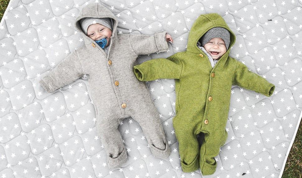 BABYBJÖRN Föräldramagasin – Tvillingbebisarna Lovisa och Matilda leker på en filt utomhus.