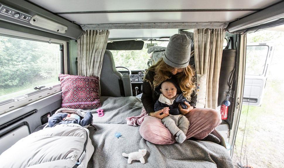 BABYBJÖRN Magazin - Mama Juli im Campervan mit einem der Babys auf dem Schoß