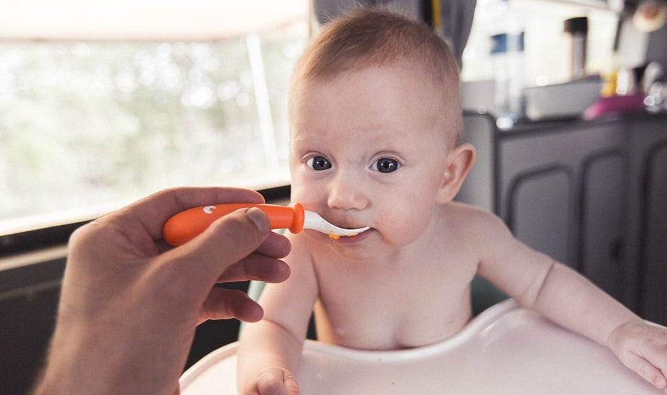 BABYBJÖRN Magazine – One of the twin babies sits in a high chair in the camper van and gets fed.
