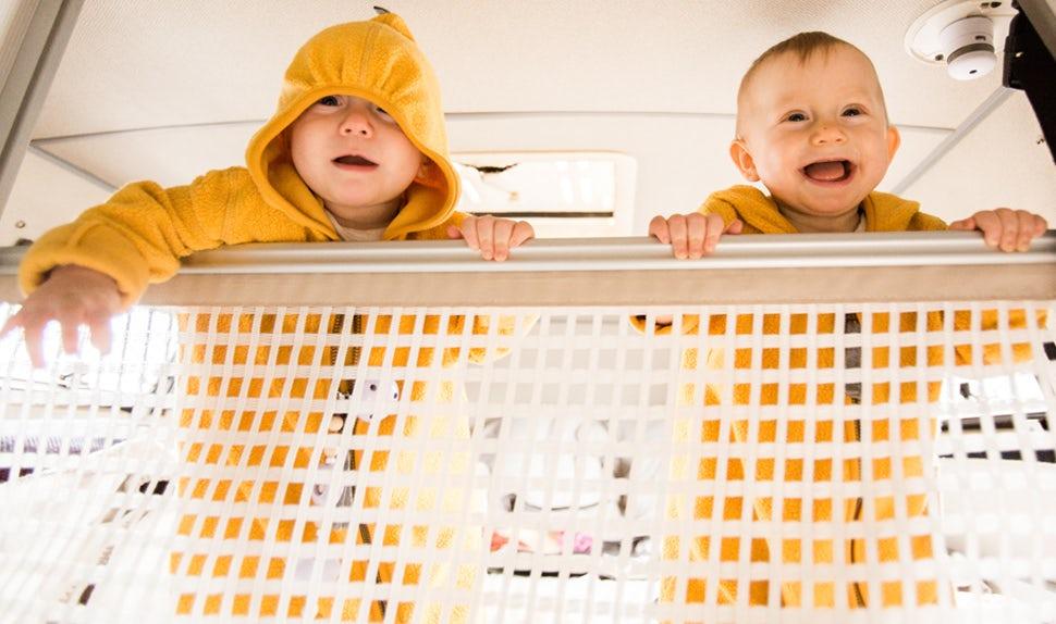 BABYBJÖRN Magazin – Die fröhlichen Zwillinge stehen am Babynetz des Bettes.