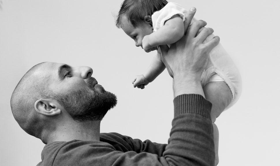 Magazine BABYBJÖRN – Récits de papas: Pierre porte dans ses bras son plus jeune enfant, sa fille Olivia.