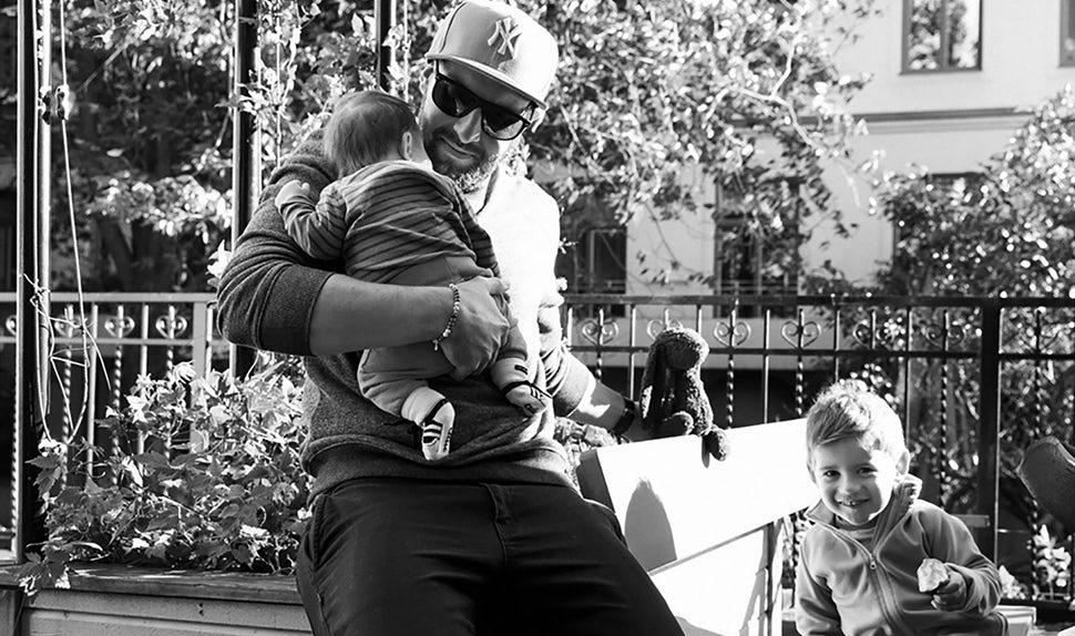 Revista BABYBJÖRN – Dadstories: el papá Pierre con sus dos hijos: la hija en el regazo y el hijo a su lado.