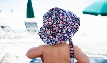 BABYBJÖRN Magazine – Kids in sunhats on the beach; travel with kids is exciting.