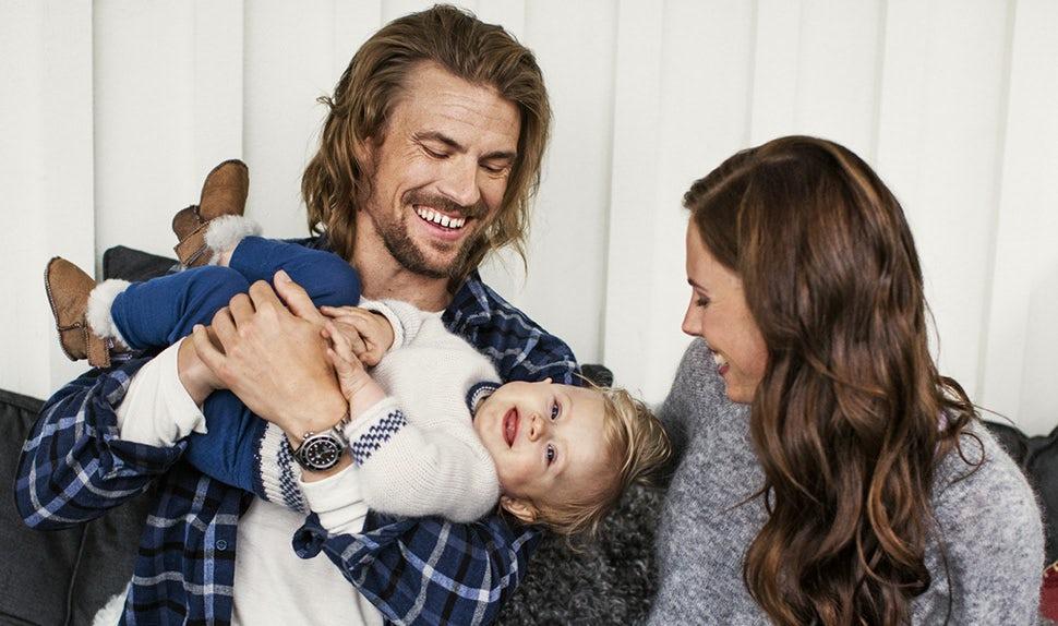 BABYBJÖRN Elternmagazin – Anna und Jacob kuscheln mit ihrer Tochter Edith nach einer Wanderung in den Bergen.