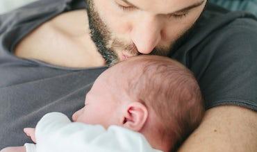 BABYBJÖRN Magazin – Baby und Schlafen: Vater streichelt den Kopf seines Babys.
