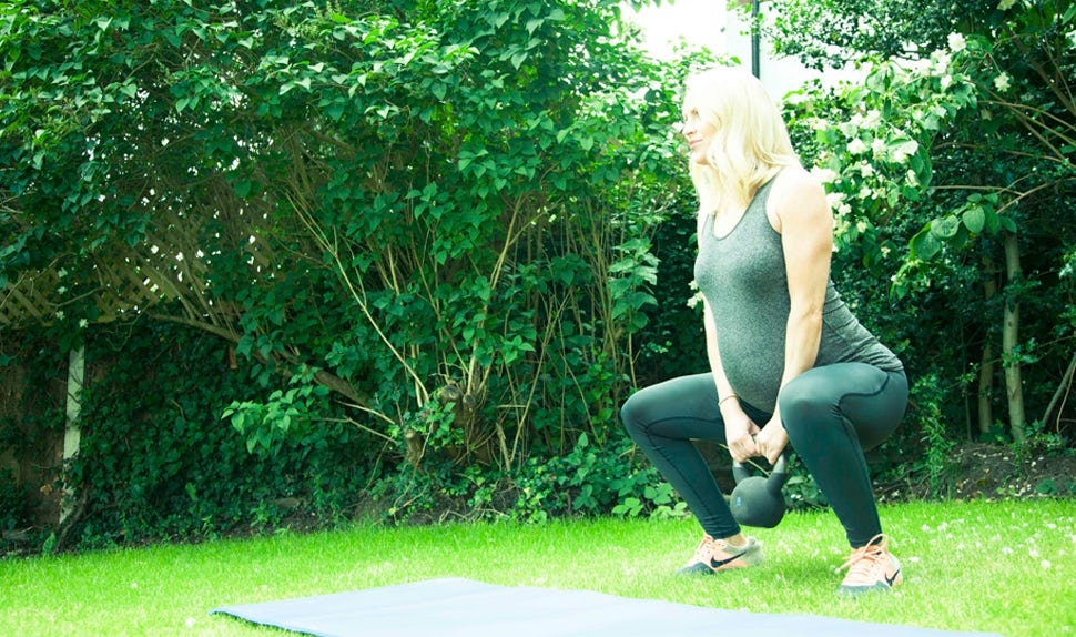 BABYBJÖRN Magazine for Parents – Pregnancy exercise: Alicia Irvine-MacDougall works out with a kettlebell in her garden.