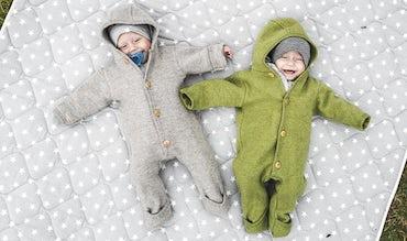 BABYBJÖRN Magazin – Die Zwillingsbabys Lovisa und Matilda spielen draußen auf einer Decke.