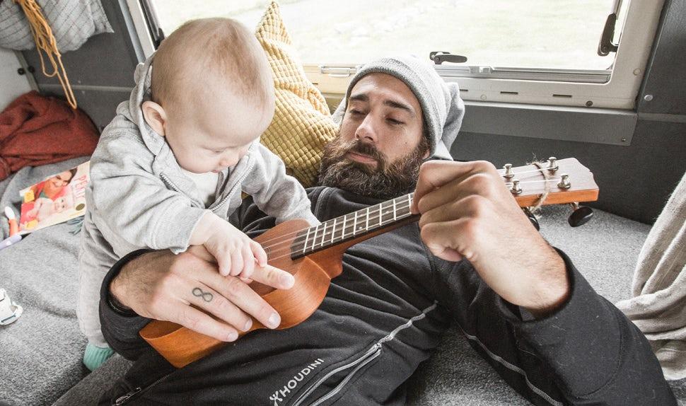 BABYBJÖRN Magazin – Papa Christian liegt auf dem Bett und spielt Ukulele. Eines der Kinder hilft ihm.