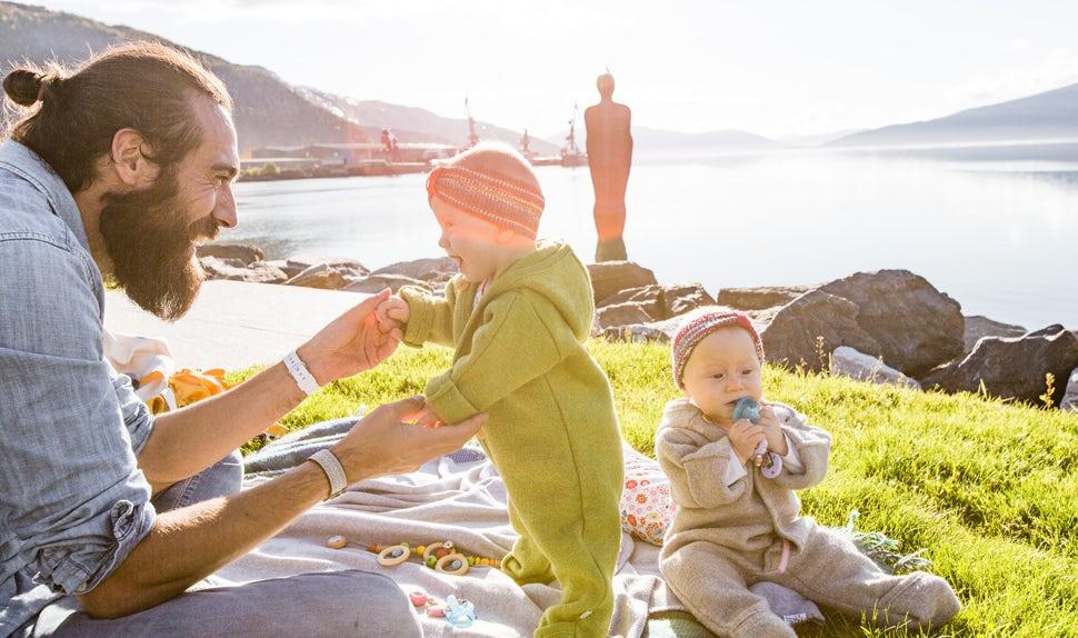 BABYBJÖRN Magazin – Die Sonne scheint und die Zwillinge spielen mit ihrem Papa auf einer Decke im Gras.