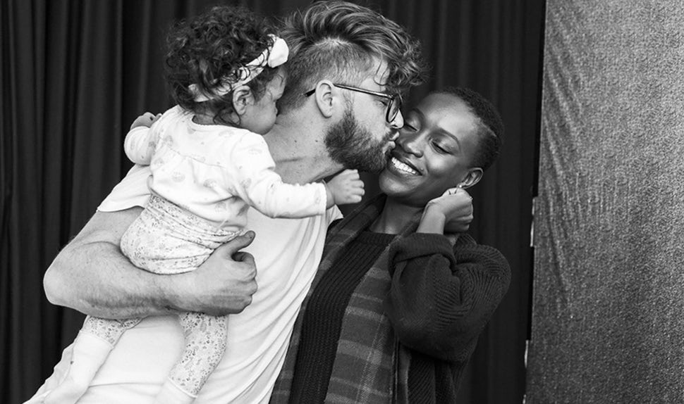 BABYBJÖRN Magazine – Dadstories: Joshua Harris with his daughter and wife captured mid-kiss.