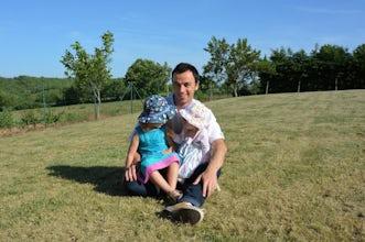 BABYBJÖRN Magazin – Die Sonne scheint und Vater Pierre sitzt mit seinen beiden Töchtern auf dem Schoß im Gras.