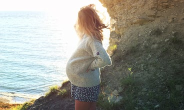BABYBJÖRN Magazine – A pregnant Klara Svensson gazes out over the sea. She's preparing for birth with hypnobirthing.